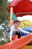 Criança feliz no campo de jogos do parque Imagem de Stock