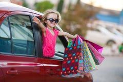 Criança feliz no carro com sacos coloridos Fotografia de Stock Royalty Free