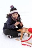 Criança feliz no pequeno trenó no inverno - pausa do chá Fotos de Stock