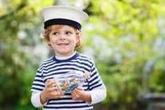 Criança feliz no uniforme do capitão que joga com navio do brinquedo Imagens de Stock Royalty Free