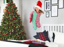 Criança feliz nos pijamas com os presentes que saltam na cama no Natal m imagens de stock