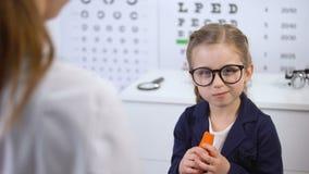 Criança feliz nos vidros que come a cenoura na recomendação do doutor, beta-carotina filme