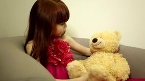 Criança feliz pequena bonito da criança da calma da menina que senta-se nas negociações da cadeira que olham lovingly no seu jogo filme