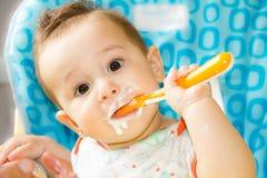 A criança feliz pequena que senta-se em uma cadeira e come o iogurte cuja da cara é estragado no comida para bebê Fotografia de Stock Royalty Free