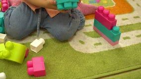 Criança feliz pré-escolar que joga com multi blocos de apartamentos coloridos no jardim de infância Educação no infantário vídeos de arquivo