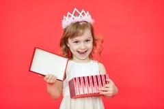 Criança feliz que abre uma caixa de presente no fundo vermelho foto de stock royalty free