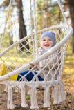 Criança feliz que balança em uma cadeira de suspensão em uma floresta imagens de stock
