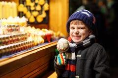 Criança feliz que come na maçã coberta com o chocolate branco no mercado do Natal Imagens de Stock Royalty Free