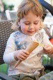 Criança feliz que come o cone de gelado com colher Fotografia de Stock