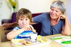 Criança feliz que come o petisco durante trabalhos de casa com avó de sorriso fotografia de stock royalty free