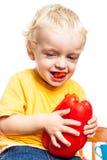Criança feliz que come a pimenta doce Fotografia de Stock