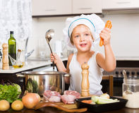Criança feliz que cozinha a sopa com vegetais Fotografia de Stock Royalty Free