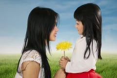 Criança feliz que dá a flor a sua mãe Fotos de Stock