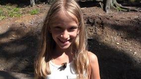 Criança feliz que estuda uma borboleta na floresta, menina de sorriso com insetos de voo 4K filme