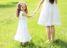 A criança feliz que guarda as mãos sere de mãe ao passeio no verão ensolarado Fotografia de Stock Royalty Free
