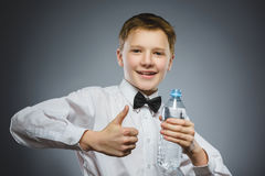 Criança feliz que guarda a garrafa da água e que mostra o polegar acima imagens de stock royalty free