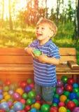 Criança feliz que joga com as bolas plásticas coloridas imagem de stock royalty free