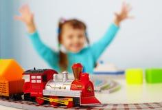Criança feliz que joga com estrada de ferro Imagem de Stock