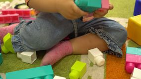 Criança feliz que joga com multi blocos de apartamentos coloridos no jardim de infância Educação no infantário filme