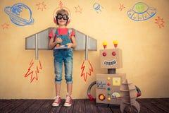 Criança feliz que joga com robô do brinquedo