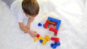 Criança feliz que joga em blocos coloridos no assoalho em um fundo branco A criança coleta o desenhador filme