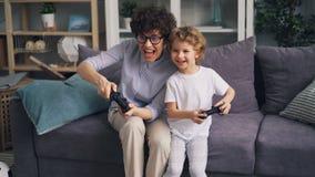 Criança feliz que joga jogos de vídeo com a mãe em casa que salta então tendo o divertimento