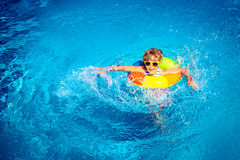 Criança feliz que joga na piscina Imagem de Stock Royalty Free