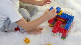 Criança feliz que joga nos blocos coloridos que sentam-se no assoalho no fundo branco Close-up A criança coleta o desenhador vídeos de arquivo