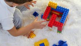 Criança feliz que joga nos blocos coloridos que sentam-se no assoalho no fundo branco A criança coleta o desenhador video estoque