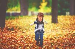 Criança feliz que joga o aviador piloto fora no outono fotografia de stock royalty free