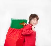 Criança feliz que leva um saco completamente de presentes do Natal, isolado no wh Imagem de Stock