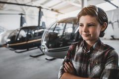 Criança feliz que localiza na exposição dos rotorcrafts foto de stock