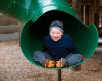 Criança feliz que monta abaixo da corrediça Fotografia de Stock Royalty Free
