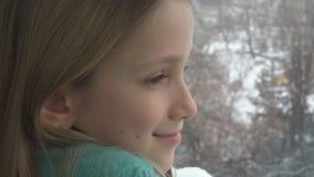 Criança feliz que olha na janela, menina da criança que sonha a luta da bola de neve, inverno do boneco de neve imagens de stock royalty free