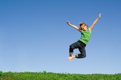 Criança feliz que salta para a alegria imagem de stock royalty free