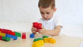 Criança feliz que senta-se na tabela que joga em blocos coloridos filme