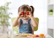 A criança feliz que tem o divertimento com os vegetais do alimento na cozinha guarda tomates antes de seus olhos como em vidros fotografia de stock royalty free