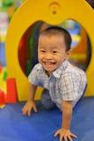 Criança feliz que tem o divertimento no campo de jogos Fotos de Stock Royalty Free