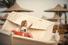 Criança feliz que tem o divertimento Rapaz pequeno da criança pouco que senta-se na boia de vida no barco fotografia de stock royalty free