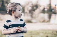 A criança feliz, rapaz pequeno olha para baixo, olhar pensativo e realizar nas mãos os crescimentos fora Espaço para o texto Retr imagem de stock royalty free
