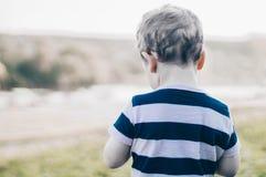 A criança feliz, rapaz pequeno olha para baixo, olhar pensativo e realizar nas mãos os crescimentos fora Espaço para o texto Retr fotos de stock royalty free