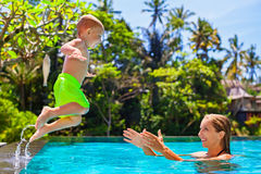 A criança feliz salta para serir de mãe às mãos na piscina Imagens de Stock