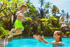 A criança feliz salta para serir de mãe às mãos na piscina Fotografia de Stock Royalty Free