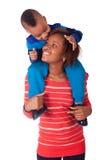 A criança feliz sorriu nos ombros de sua matriz Foto de Stock Royalty Free