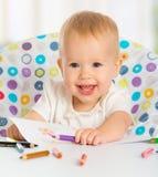 A criança feliz tira com os pastéis coloridos dos lápis Imagem de Stock