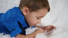 A criança feliz usa contentemente um smartphone para jogos, encontrando-se em um sofá branco filme