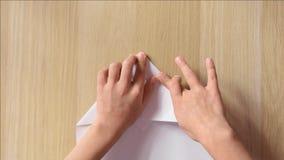 A criança fez um avião fora de uma folha de papel, modo rápido vídeos de arquivo
