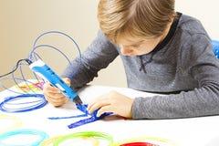 Criança focalizada com a pena da impressão 3d que cria um plano Fotografia de Stock Royalty Free