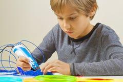 Criança focalizada que cria com a pena da impressão 3d Foto de Stock