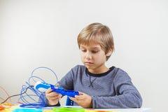 Criança focalizada que cria com a pena da impressão 3d Imagens de Stock Royalty Free